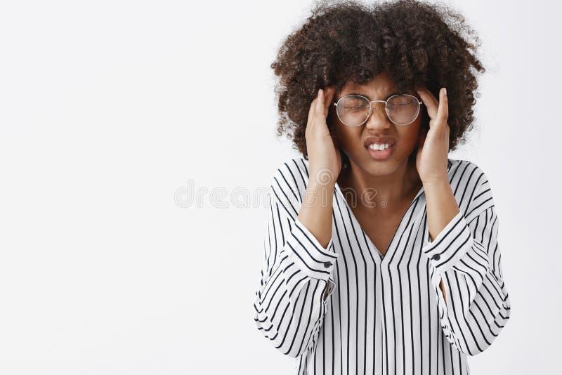 O incômodo de pele escura interessado do sentimento da mulher não pode focalizar da dor de cabeça ou recordar o closing da inform foto de stock