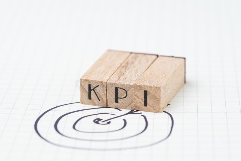 O indicador de desempenho chave, conceito de KPI, selo de madeira pequeno combina o acrônimo KPI com a seta da tração da mão e o  fotografia de stock royalty free