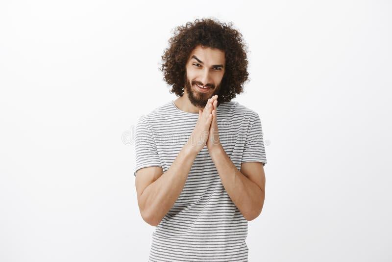 O indivíduo ávido tem o plano desagradável Retrato do homem encaracolado-de cabelo intrigado com barba, palmas de fricção junto p imagem de stock