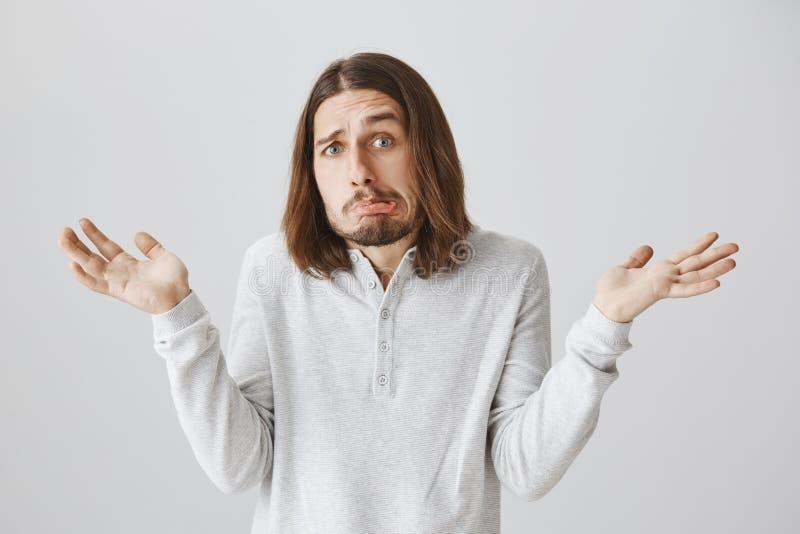 O indivíduo é confundido com as perguntas O estúdio disparou do homem engraçado considerável com a barba e o cabelo longo que faz imagens de stock