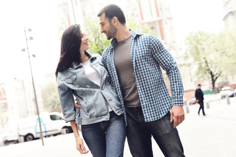 O indivíduo abraça a mulher da cintura no revestimento da sarja de Nimes fotografia de stock