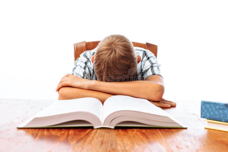 O indivíduo adolescente caiu assento adormecido com livros, estudante que dorme na mesa no estúdio no fundo branco imagem de stock