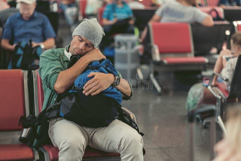 O indivíduo adulto cansado está adormecido no banco fotografia de stock