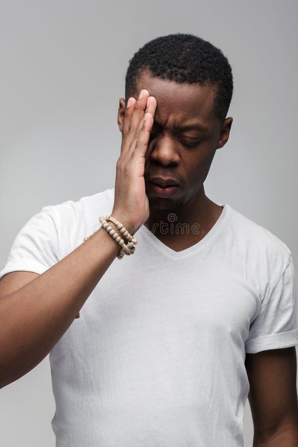 O indivíduo afro-americano preocupado sente triste e incomodado foto de stock