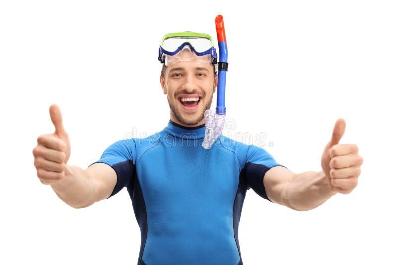 O indivíduo alegre em um roupa de mergulho que faz os polegares levanta o gesto imagem de stock royalty free