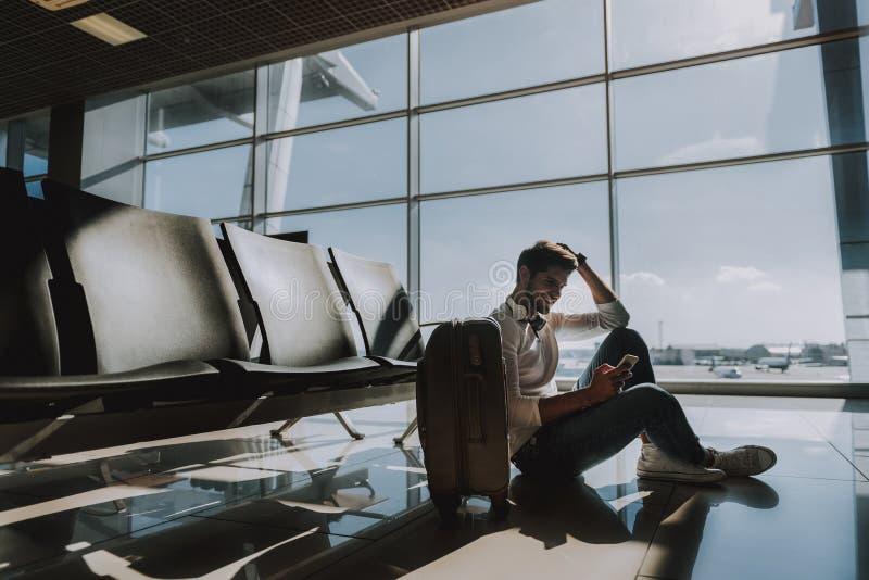 O indivíduo alegre está usando o telefone esperto no aeroporto fotografia de stock