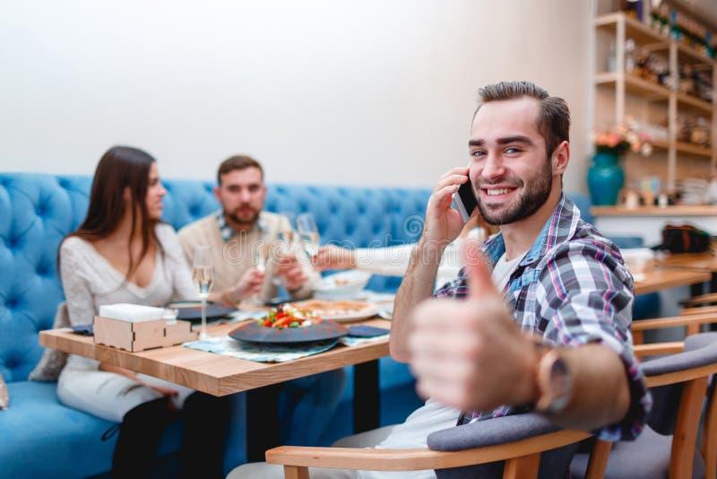 O indivíduo alegre fala no telefone e mostra seu polegar acima, sentando-se em um café com amigos fotografia de stock royalty free