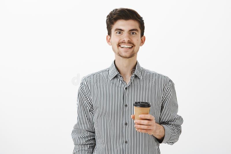 O indivíduo amigável encantador trouxe o café ao colega de trabalho que gosta Retrato do noivo bonito satisfeito na camisa, sorri imagem de stock