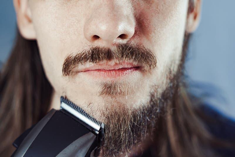 O indivíduo barbeia sua barba com uma lâmina elétrica fotografia de stock