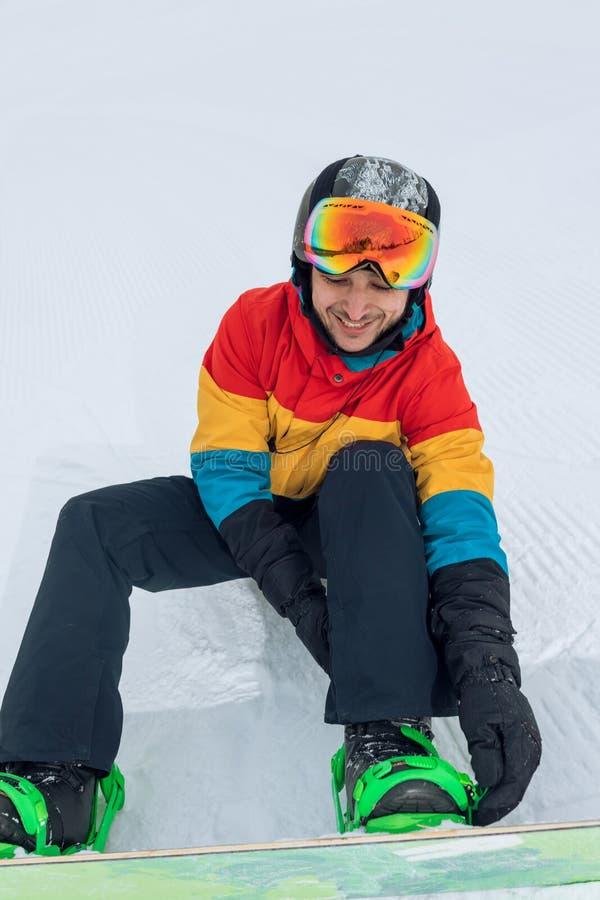 O indivíduo bonito aprecia pôr sobre botas para a snowboarding fotografia de stock royalty free