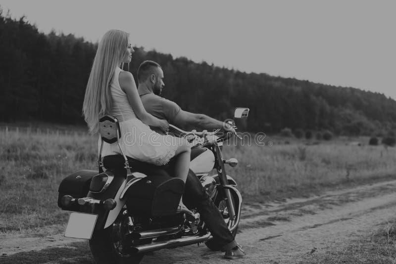 O indivíduo com a menina em um campo em uma motocicleta imagem de stock royalty free