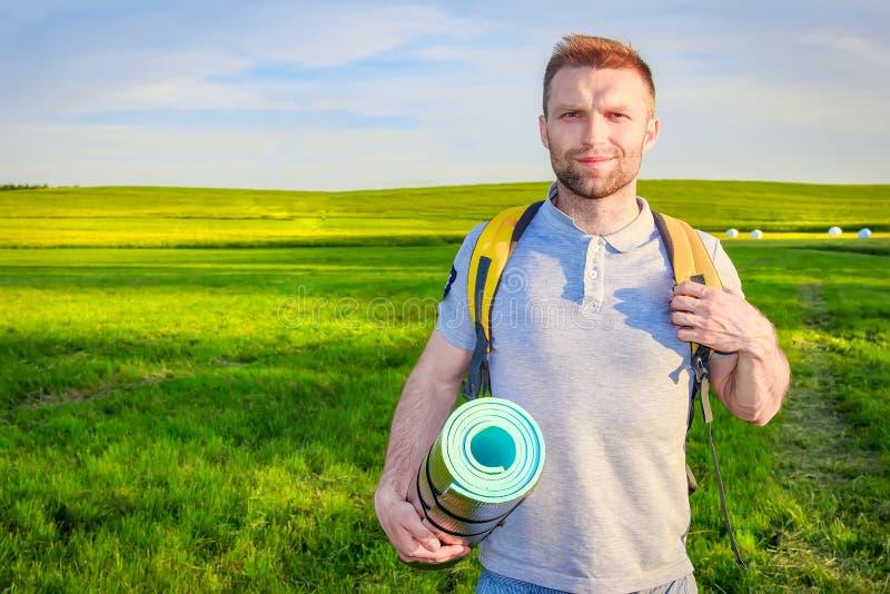 O indivíduo com trouxa vai tomar parte num piquenique no fundo do prado verde acampar Um homem novo vai na caminhada imagens de stock