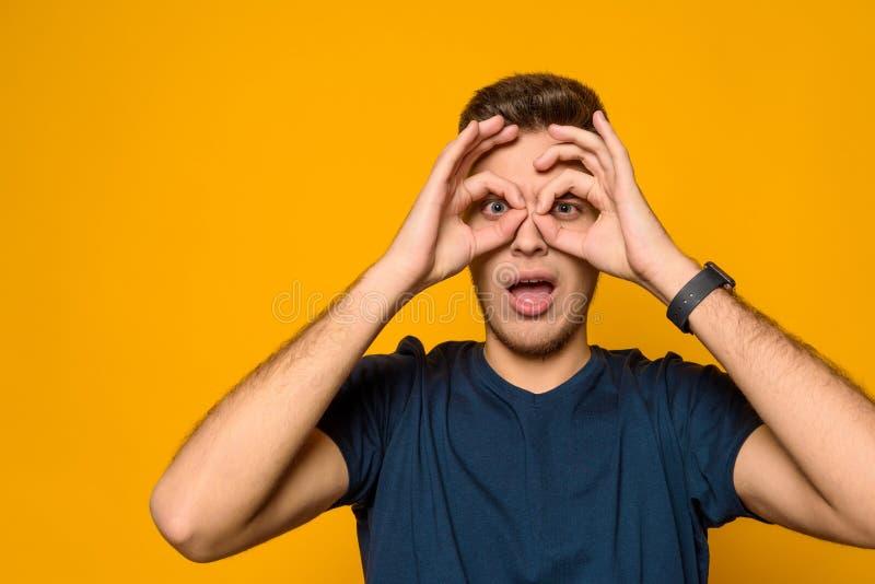 O indivíduo considerável novo mostra o binocle do gesto isolado imagens de stock