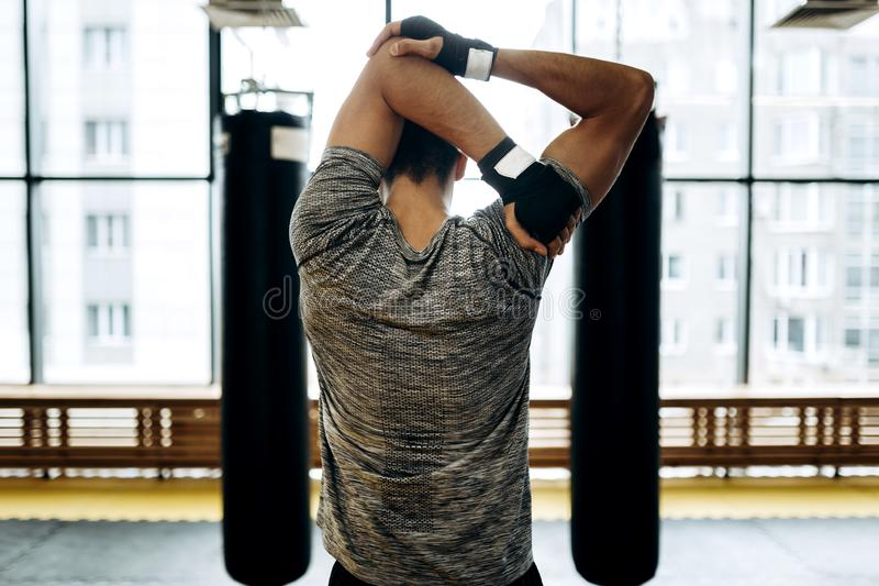 O indivíduo de cabelo escuro estica seus braços no gym entre dois sacos de perfuração no fundo de janelas panorâmicos fotos de stock