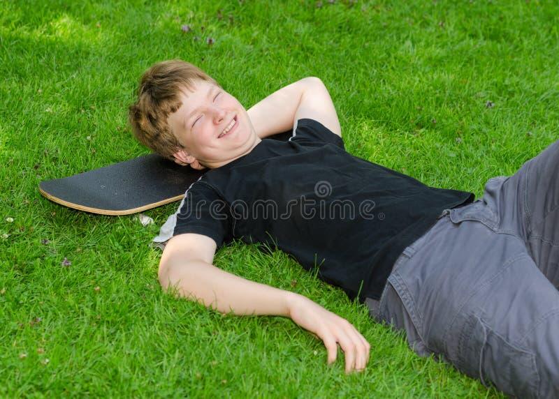 O indivíduo de riso relaxa no skate na grama do parque foto de stock