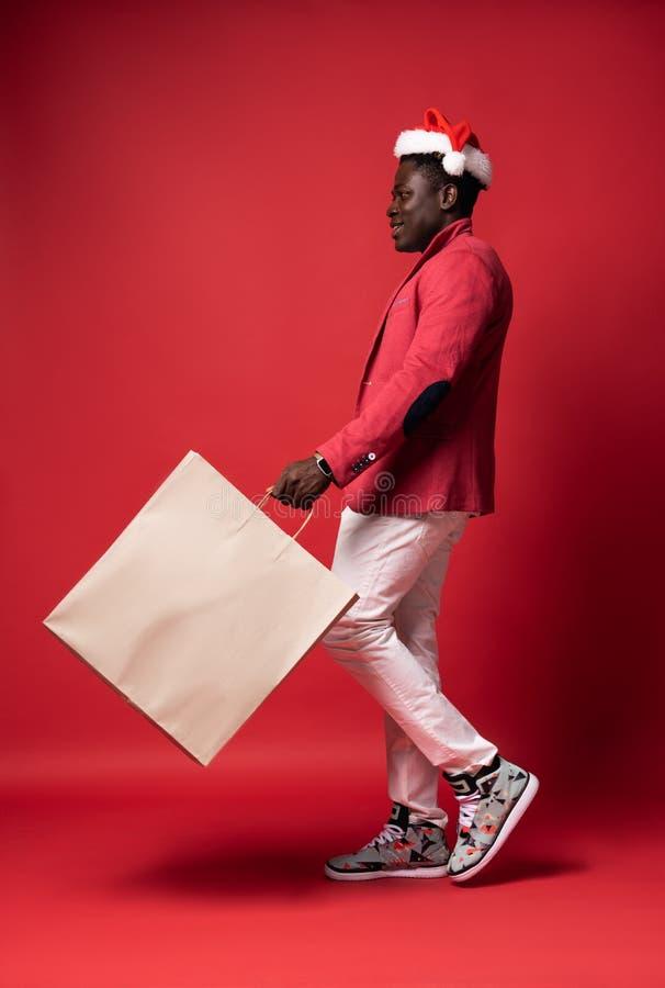 O indivíduo de sorriso está guardando o saco de papel branco fotografia de stock royalty free