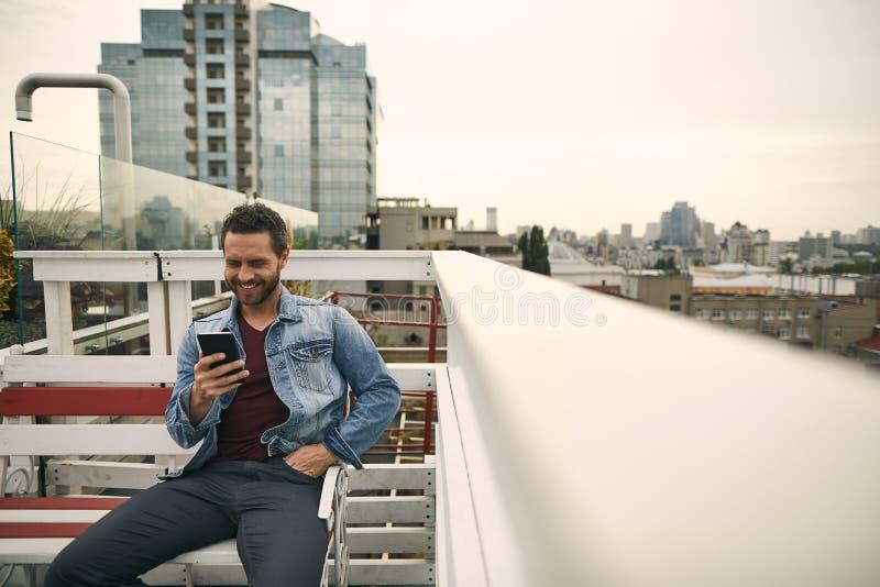 O indivíduo de sorriso está sentando-se em um banco imagem de stock
