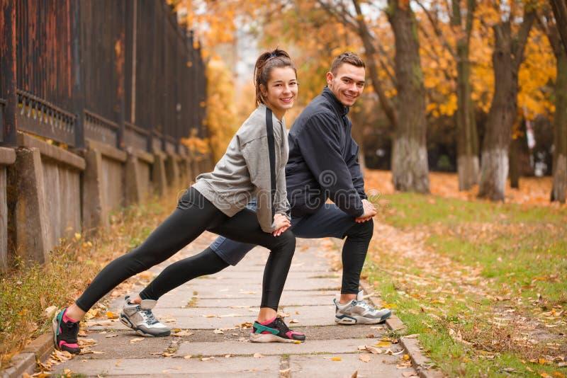 O indivíduo desportivo e a menina que fazem o pé jogam exercícios no parque outdoors fotografia de stock