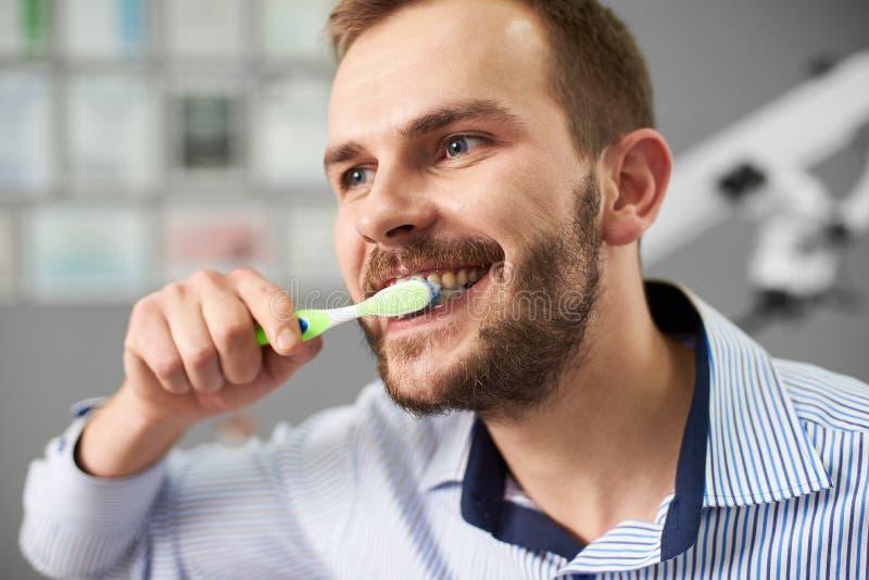 O indivíduo do close-up com barba limpa seus dentes no escritório dental imagens de stock royalty free
