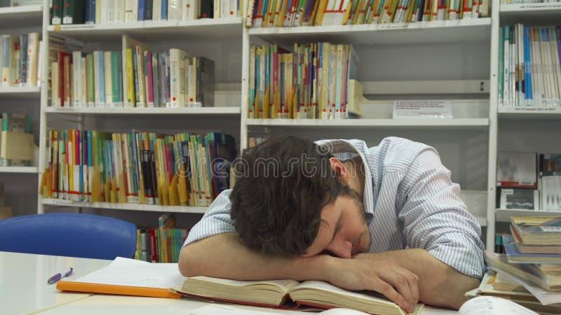 O indivíduo dorme na biblioteca foto de stock royalty free