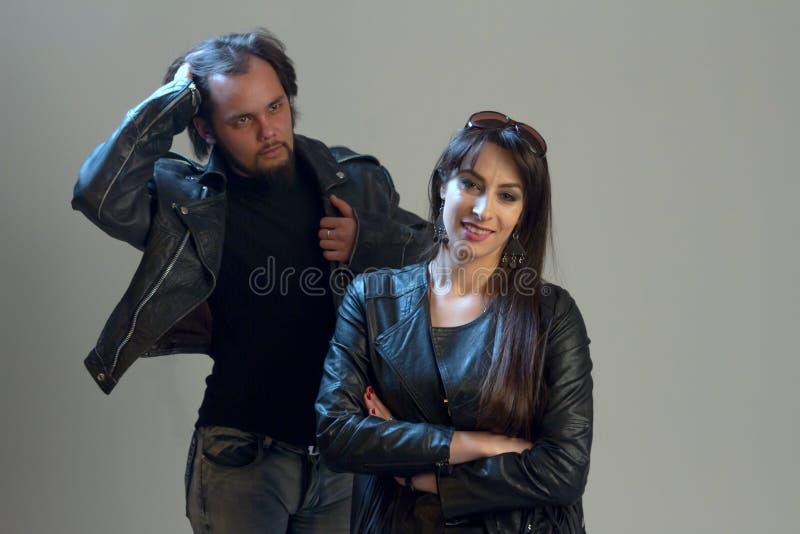 O indivíduo e a menina na roupa de couro preta Jovens à moda elegantes modernos Estilo do balancim ou do motociclista foto de stock