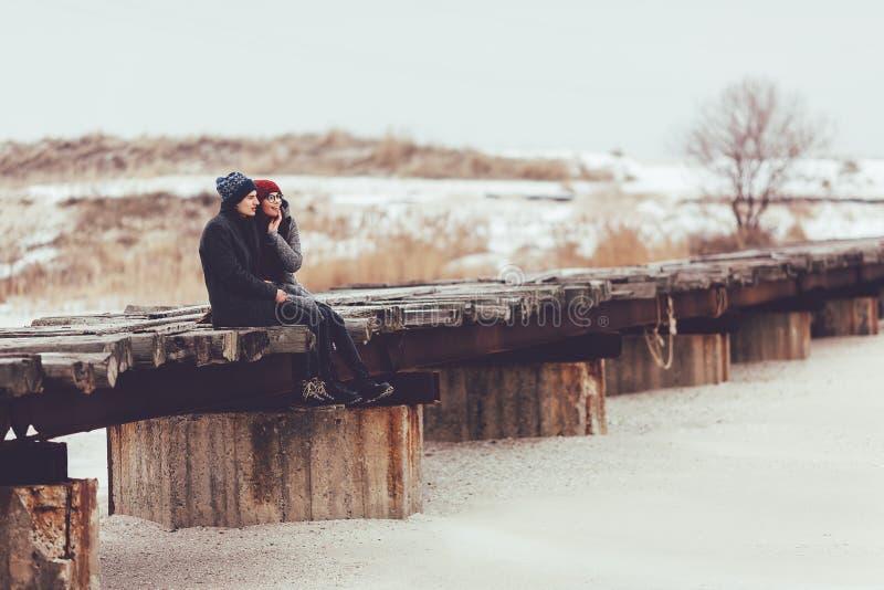 O indivíduo e a menina novos no desgaste do inverno, abraço e apreciam o cenário do inverno imagem de stock royalty free