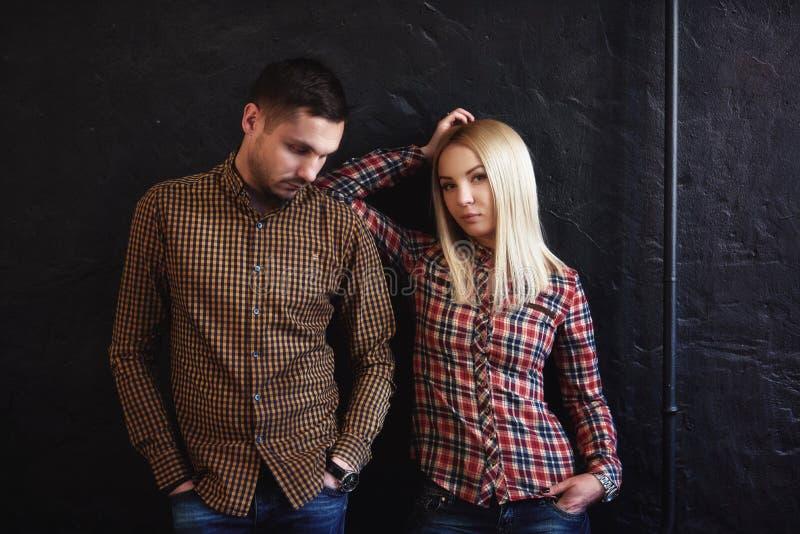 O indivíduo e a menina que estão pensativamente perto da parede escura foto de stock