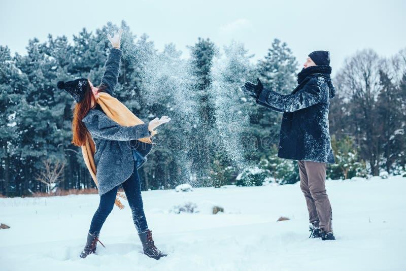 O indivíduo e a menina têm um resto nas madeiras do inverno Marido e esposa na neve Pares novos que andam no parque do inverno foto de stock royalty free