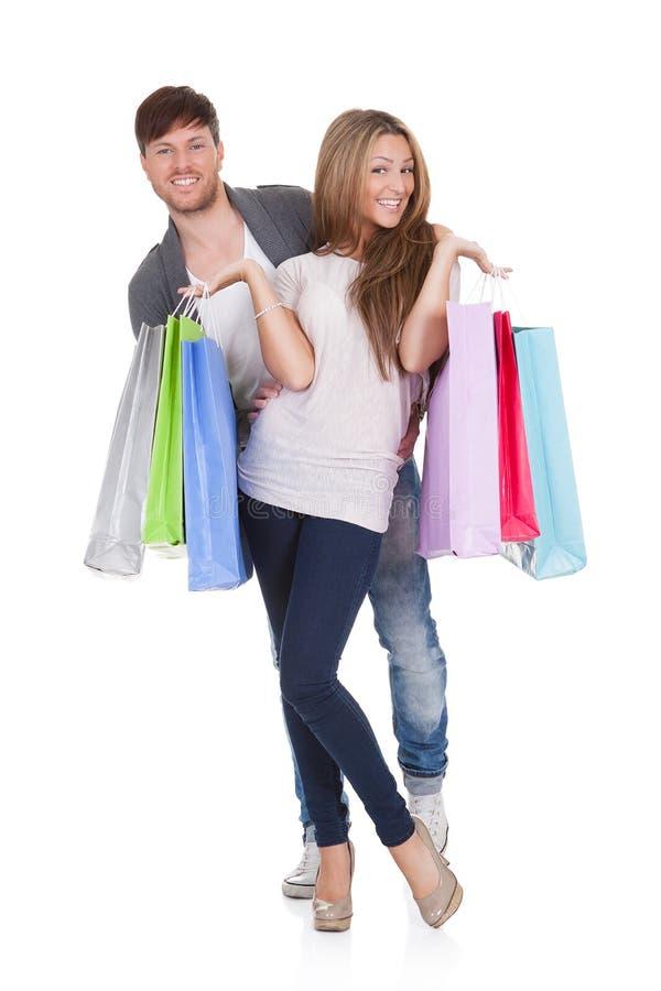 O indivíduo e o galão trazem sacos de compras imagem de stock royalty free