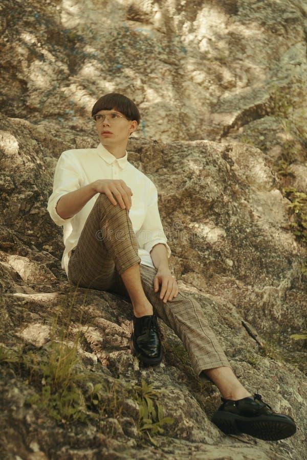 O indivíduo elegante do moderno está sentando-se nas rochas Homem do moderno com um corte de cabelo elegante Homem em vidros fres fotografia de stock