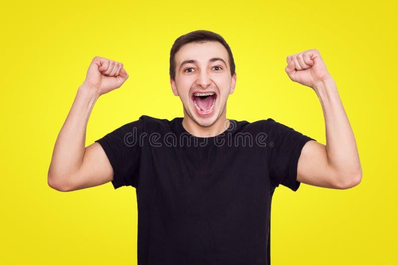 O indivíduo em um t-shirt preto exulta a vitória, levanta suas mãos acima, isolado fotos de stock