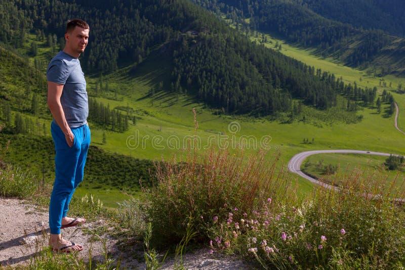 O indivíduo em um t-shirt verde está estando na borda do penhasco na parte traseira dele é uma vista colorida das montanhas e de  fotografia de stock