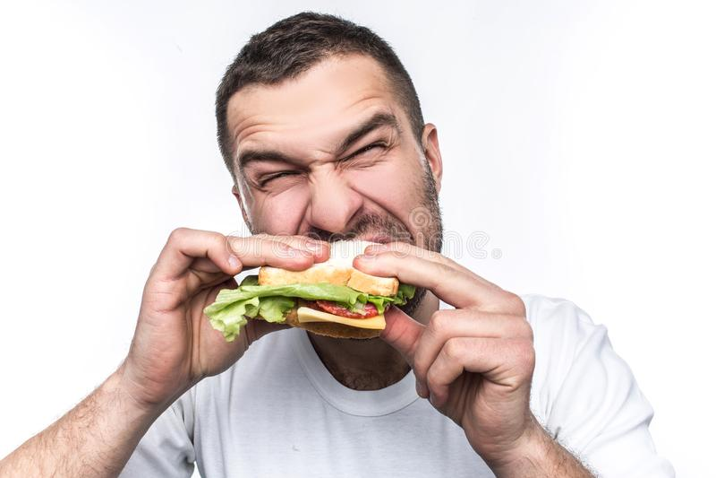 O indivíduo engraçado e com fome está comendo algum fast food Está com fome como um lobo O homem é sanduíche cortante muito duro  fotografia de stock royalty free