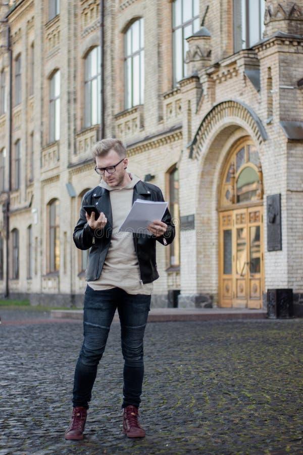 O indivíduo esperto concentrado na roupa ocasional guarda papéis e olhares no telefone ao estar ao lado da universidade fotos de stock