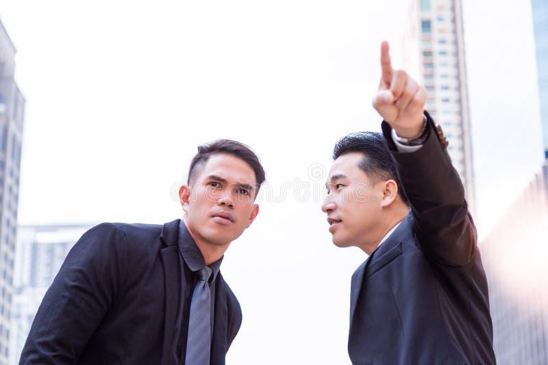 O indivíduo está dizendo a maneira ao homem de negócios novo considerável e à probabilidade de intercepção fotografia de stock royalty free