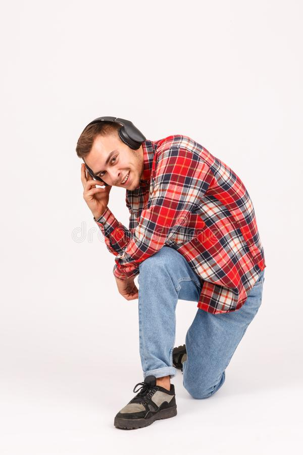 O indivíduo está em um joelho e as posses uma cedem os fones de ouvido em um fundo cinzento Front View fotos de stock royalty free
