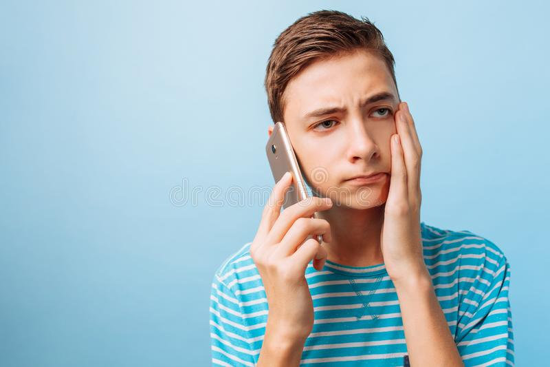 O indivíduo está falando no telefone, a virada pelo que se ouviu, em um fundo azul imagens de stock