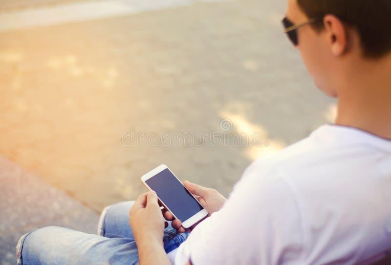 O indivíduo está guardando um smartphone móvel e está olhando a tela dependência do telefone, redes sociais Trabalho no Internet  imagem de stock