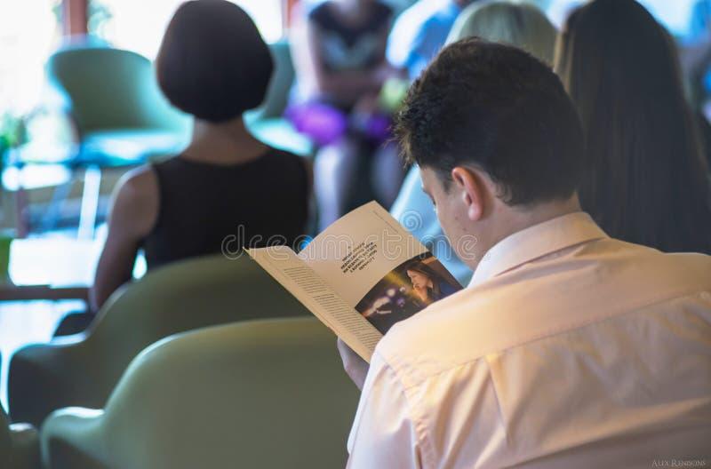 O indivíduo está lendo um livro em uma conferência imagens de stock royalty free