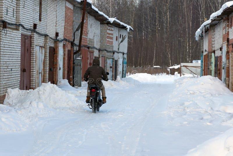 O indivíduo está montando uma motocicleta no inverno imagens de stock royalty free
