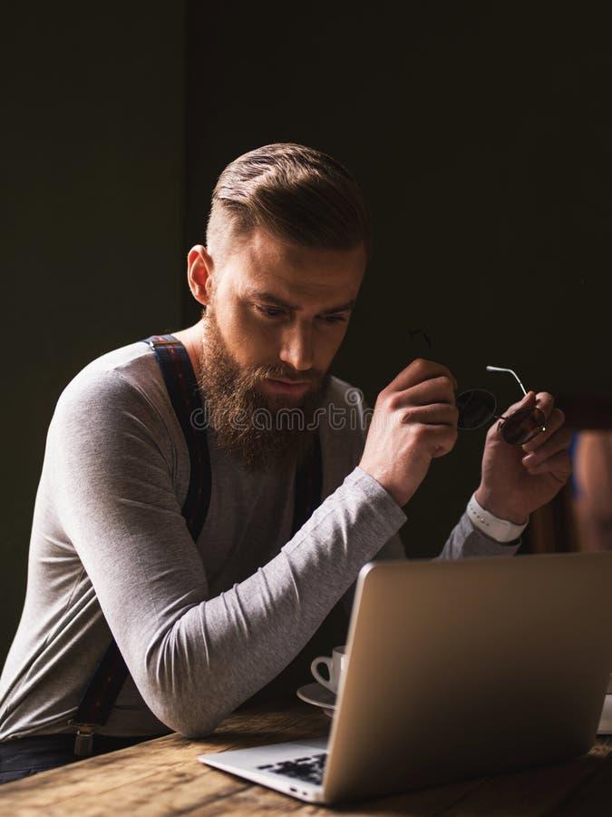 O indivíduo farpado alegre está trabalhando com um portátil imagens de stock