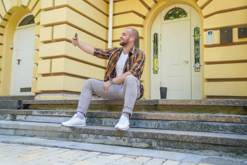 O indivíduo farpado corajoso bonito novo está sentando-se fora em escadas na frente de sua casa que faz o selfie e o sorriso Tem foto de stock royalty free