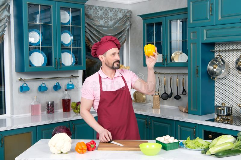 O indivíduo farpado no avental vermelho e no chapéu vermelho olha a paprika amarela imagens de stock