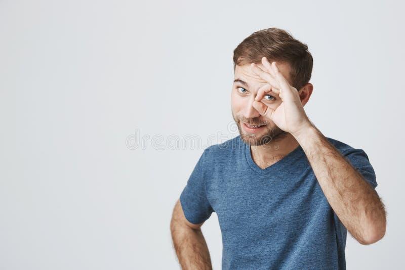 O indivíduo farpado positivo no t-shirt azul mostra o sinal aprovado, demonstra que tudo é muito bem, concorda Homem alegre segur fotos de stock
