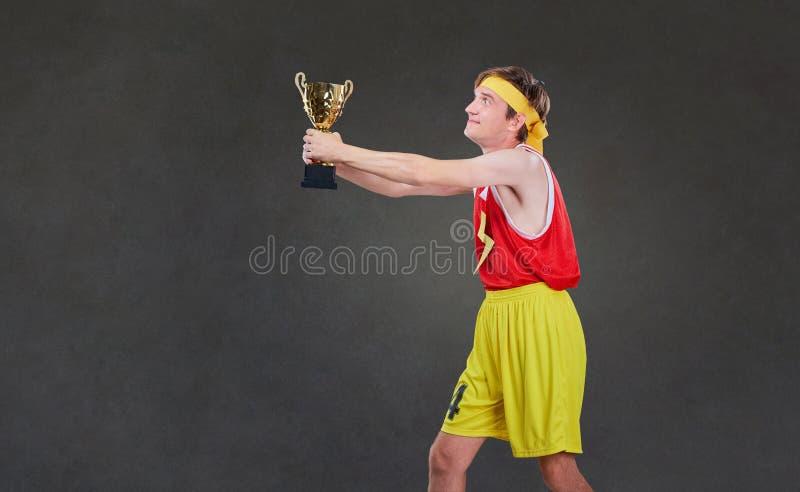 O indivíduo fino engraçado nos esportes veste-se com um copo do campeonato no seu foto de stock