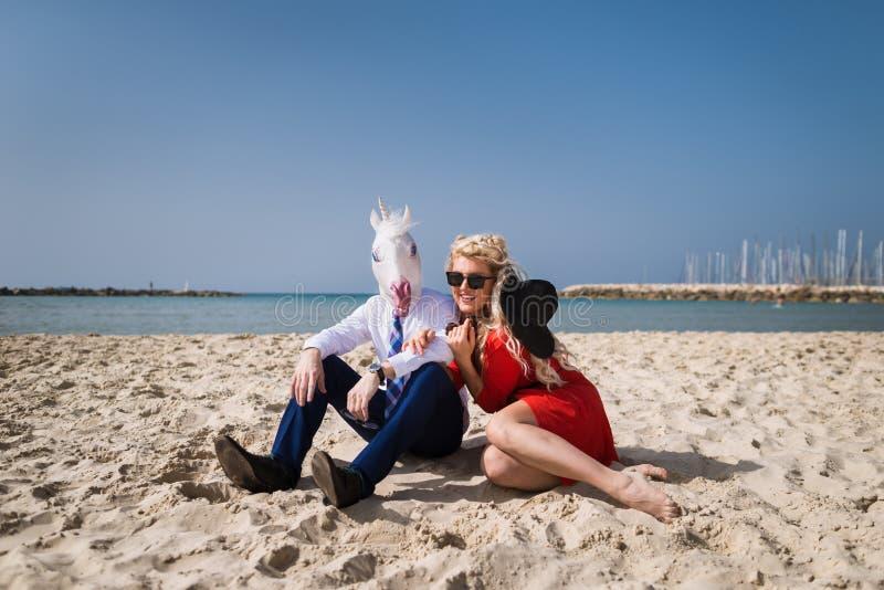 O indivíduo Freaky no terno e na máscara engraçada senta-se com a menina bonita no vestido vermelho fotos de stock