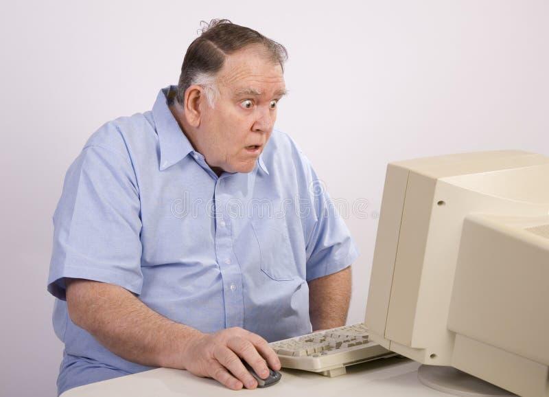 O indivíduo idoso no computador espantou-se fotografia de stock royalty free