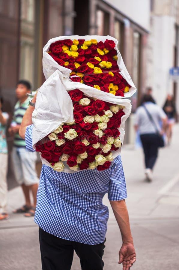 O indivíduo leva um ramalhete grande com as rosas vermelhas, brancas e amarelas fotografia de stock