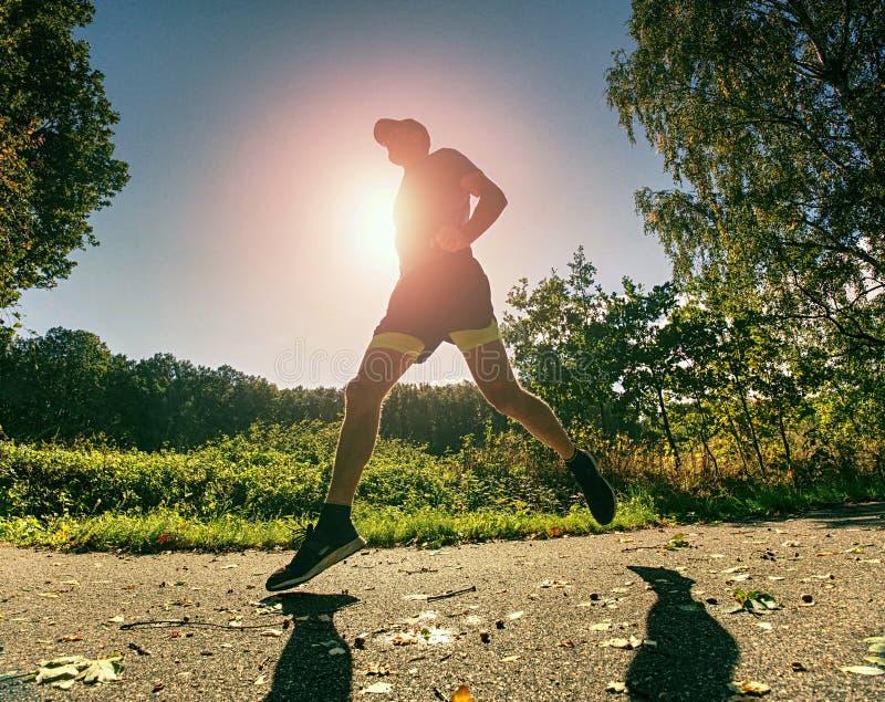O indivíduo magro do corpo corre no trajeto com folhas caídas Dia morno fotos de stock