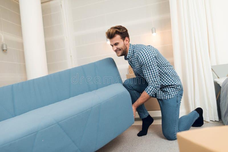 O indivíduo move o sofá ao transportar-se a uma casa nova O indivíduo faz uma reconstituição na sala imagem de stock